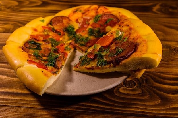 素朴な木製のテーブルにスライスした自家製ピザとセラミックプレート