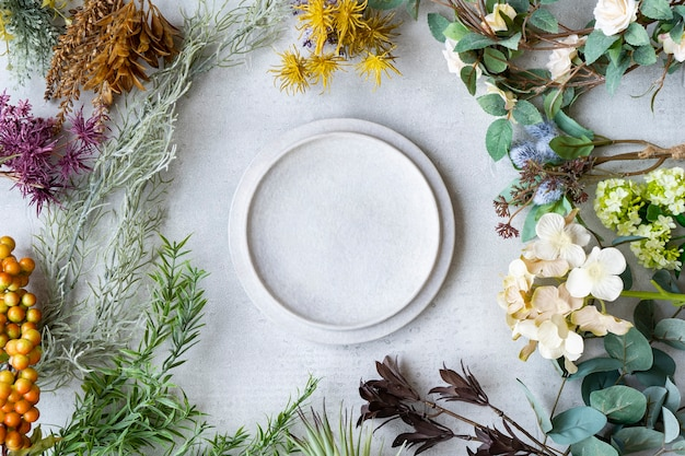 大理石のテーブルに置かれたセラミックプレートと植物の装飾品