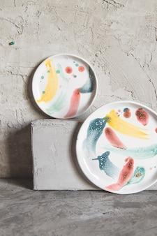 Керамические тарелки, расписанные красками, на сером фоне.