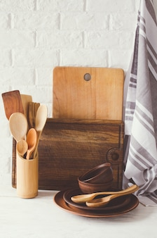 Ceramic plates, wooden or bamboo cutlery, cutting boards and towel in interior of kitchen.