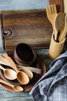 Ceramic plates, wooden or bamboo cutlery, vintage cutting board and towel in interior of kitchen.