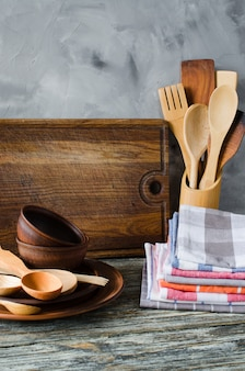 Ceramic plates, wooden or bamboo cutlery, vintage cutting board and towels in interior of kitchen.