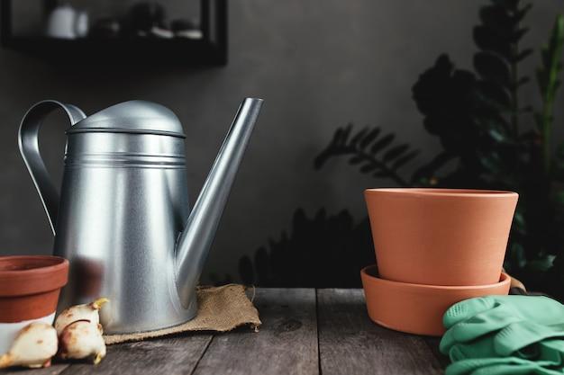오래 된 회색 나무 테이블, 튤립 구근, 물을 수, 녹색 장갑 및 정원 삽에 세라믹 냄비. 고품질 사진