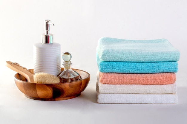 Ceramic soap, shampoo bottles and white cotton towels on white background.