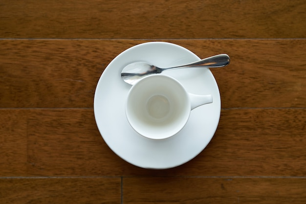 Ceramic tea or coffee cup with spoon and plate on wooden palette