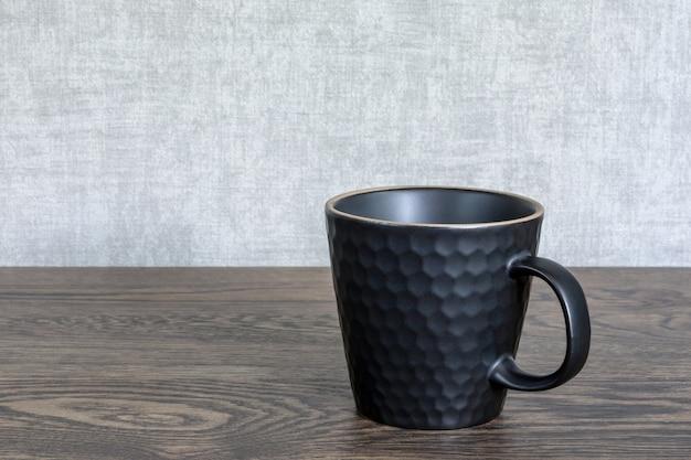 木製のテーブルの上のセラミックティーカップ。ホットドリンク用の黒い皿