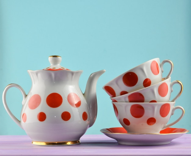 Ceramic teapot, a stack of cups in polka dots on a wooden table isolated. copy space