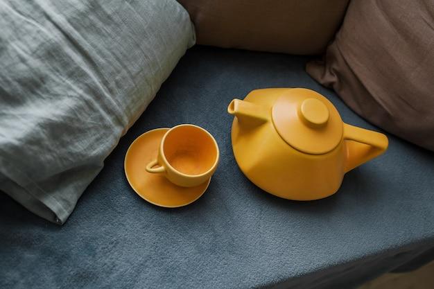 Керамический чайник с чашками на диване. современный чайник. заваривание чая. яркое фото. чайная церемония