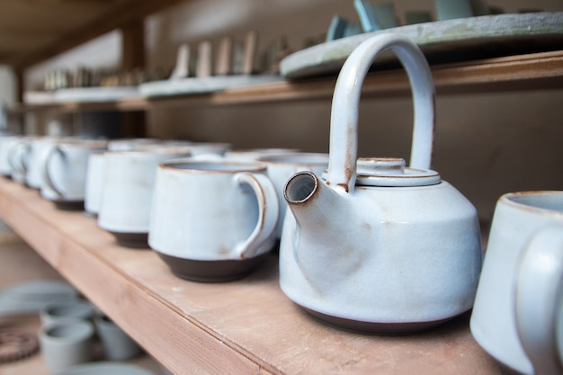 Ceramic teapots in the pottery workshop on the rack. handmade blue ceramic teapots