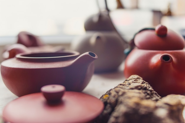 Ceramic teapots stand on a window in a cafe