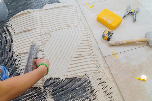 Керамическая плитка и инструменты для плиточника. установка напольной плитки. домохозяйство, ремонт