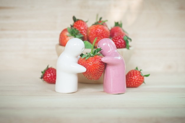 Ceramic toy giving a strawberry to couple for their love
