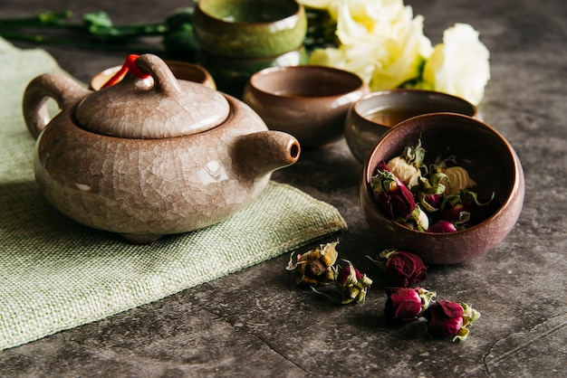 Ceramic traditional teapot with teacups and dried rose on concrete backdrop