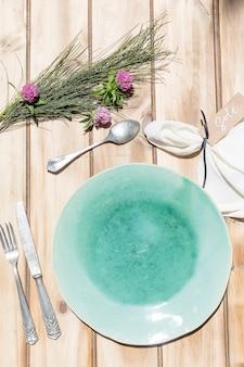 木製のテーブルにセラミックターコイズプレートとカトラリー