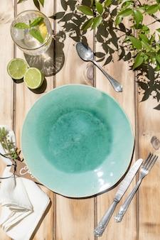 セラミックターコイズプレート、木製のテーブルにレモネードとカトラリーとガラス