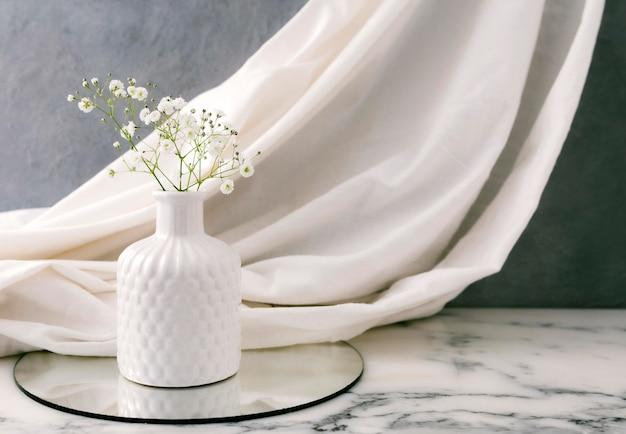 テーブルの上に花が付いている陶製の花瓶