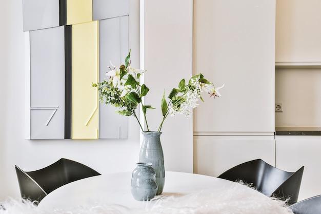 自宅のスタイリッシュなダイニングルームの椅子の近くのテーブルに置かれた花の枝を持つセラミック花瓶