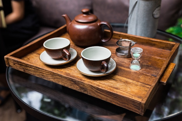 Ceramic vintage cups, mug and small sand clock, equipment for making dry flower with tea stainless steel tea strainer infuser in wooden tray.
