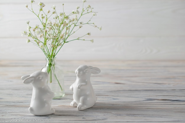Ceramic white bunnies on white wooden table with fresh white spring flowers