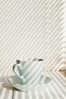 Ceramic white coffee cup with saucer near on wooden table