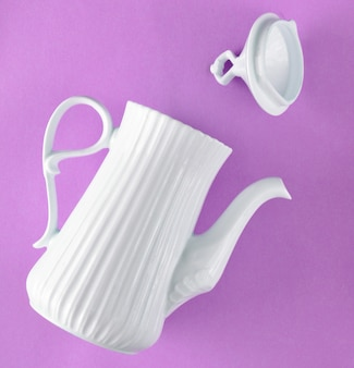 Ceramic white teapot on purple pastel background