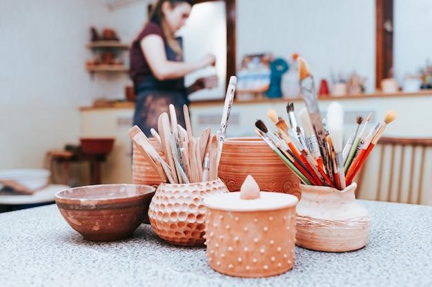 Ceramics master prepares to paint pottery.