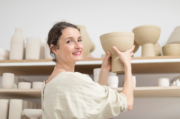 Ceramist woman holding a potter in her studio