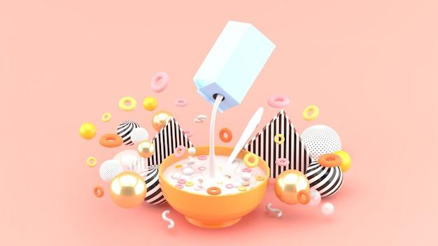 ピンクの空間にあるカラフルなボールの中にシリアルとミルクがあります