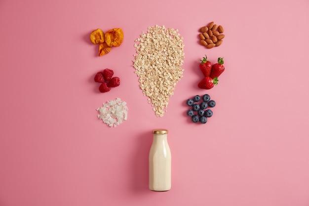 朝の食事を作るためのシリアルと様々なおいしい食材。朝食においしいお粥を作るための植物ベースのミルク、オーツ麦、ベリー、ドライフルーツ。健康的なライフスタイル、栄養、フィットネスの概念