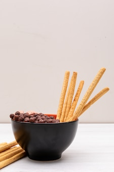 Cereal balls with bread sticks in bowl on white surface