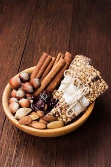 ナッツ、ベリー、シナモンの木製の背景を持つ穀物バー