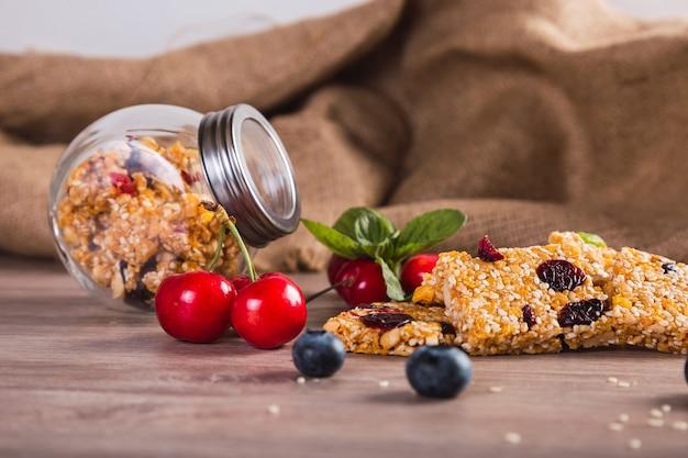 健康的な食事のための赤い果物、蜂蜜、ゴマのシリアルバー-素朴な背景にさくらんぼ、種子、蜂蜜の自家製ベジタリアングラノラバー。
