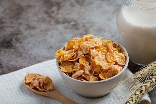 Cereal in bowl and milk on dark background