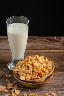 Cereal in bowl and milk on dark wooden background