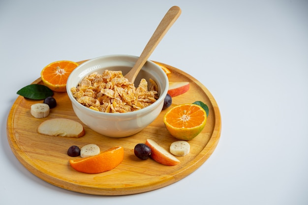 Cereal in bowl and mixed fruit on marble background