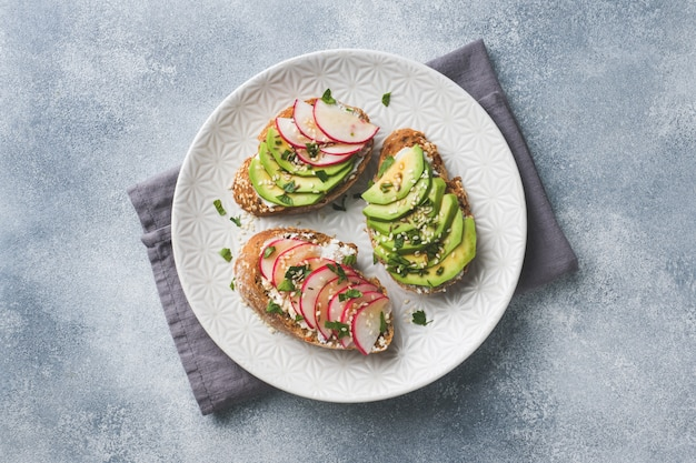 Cereal bread sandwiches with cottage cheese, fresh avocado and radish.
