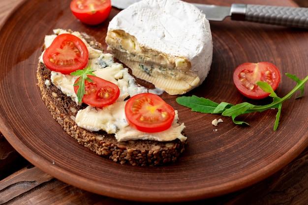 Зерновой хлеб с голубым сыром и помидорами черри на глиняной тарелке на деревянном фоне. здоровое вегетарианское питание.