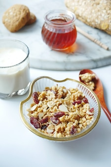 Cereal breakfast in bowl honey and milk on white background