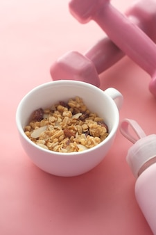 Cereal breakfast and dumbbell in bowl on pink background