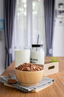 Cereal breakfast with glass of milk, bottle of milk on wood table in living room.