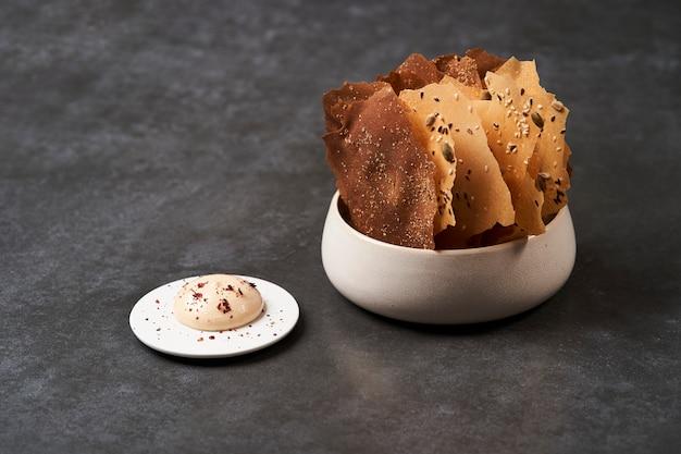 Зерновые чипсы с семенами и соусом кимчи майонез на темном фоне
