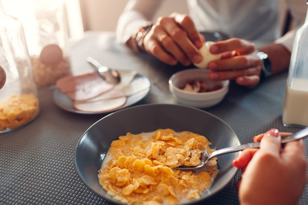 Cereal cornflake with milk breakfast. family couple eating healthy food. man peeling eggs.