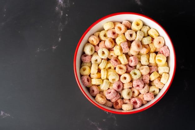 복사 공간, 아침 개념 빨간색 그릇에 시리얼 조각. 맛있는 과일 맛과 과일 색상의 음식. 그것은 옥수수, 밀, 보리로 만들어졌습니다. 빨간색 그릇과 어두운 배경에서 시리얼 조각.
