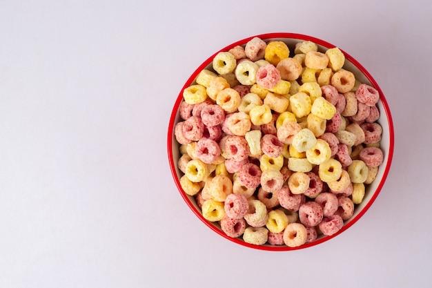 복사 공간, 아침 개념 빨간색 그릇에 시리얼 조각. 맛있는 과일 맛과 과일 색상으로 음식. 그것은 옥수수, 밀, 그리고 barley.topview 및 복사 space.white 배경으로 만들어졌습니다.