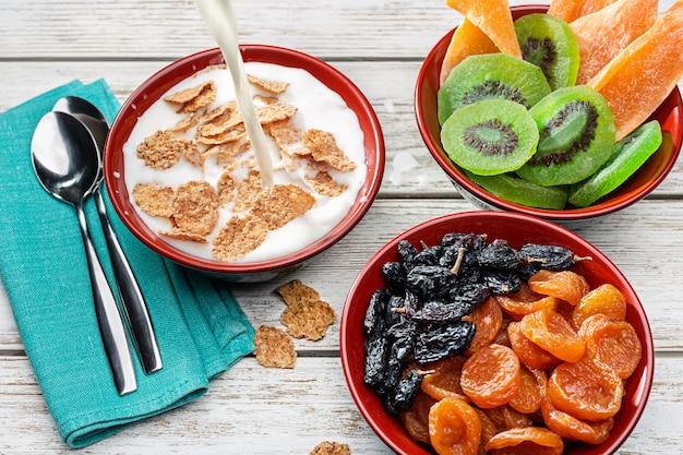 Зерновые хлопья с молоком, сушеными киви, манго, абрикосами и изюмом в трех деревянных мисках. утренний натюрморт на белом деревянном столе.