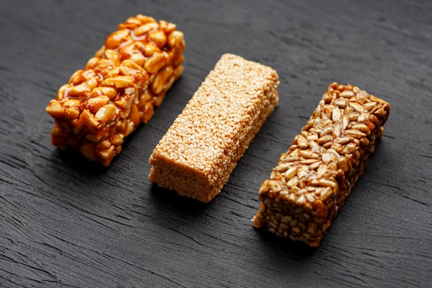 Cereal granola bar with peanuts, sesame and sunflower seeds on a cutting board on a dark stone table. view from above. three assorted bars