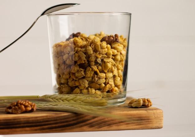 Зерновые мюсли в прозрачном стакане с шипом ржи, ложкой и грецкими орехами на полке на белом фоне.