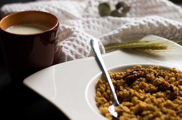 Зерновые мюсли в белой тарелке с ложкой и глиняным стаканом молока на черной деревянной столешнице. выборочный фокус