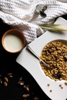 Зерновые мюсли в белой тарелке с ложкой и глиняным стаканом молока на черной деревянной столешнице. вертикальный. вид сверху. селективный фокус