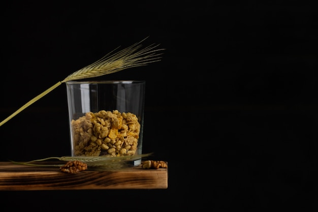 Cereal granola in a transparent glass with rye spike and walnuts on a shelf on a black background. copy space.